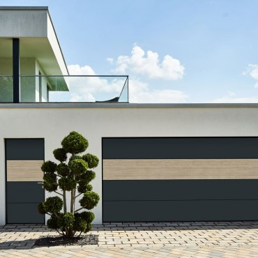 Entrance and garage of a house in minimalist design, with an unnaturally trimmed tree